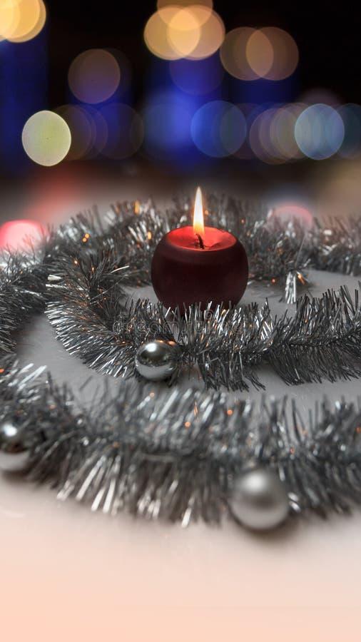 Ευχετήρια κάρτα φιαγμένη από ασημένιο tinsel με τις ασημένιες σφαίρες Χριστουγέννων, το κόκκινο καίγοντας κερί και bokeh τα φω'τα στοκ εικόνες