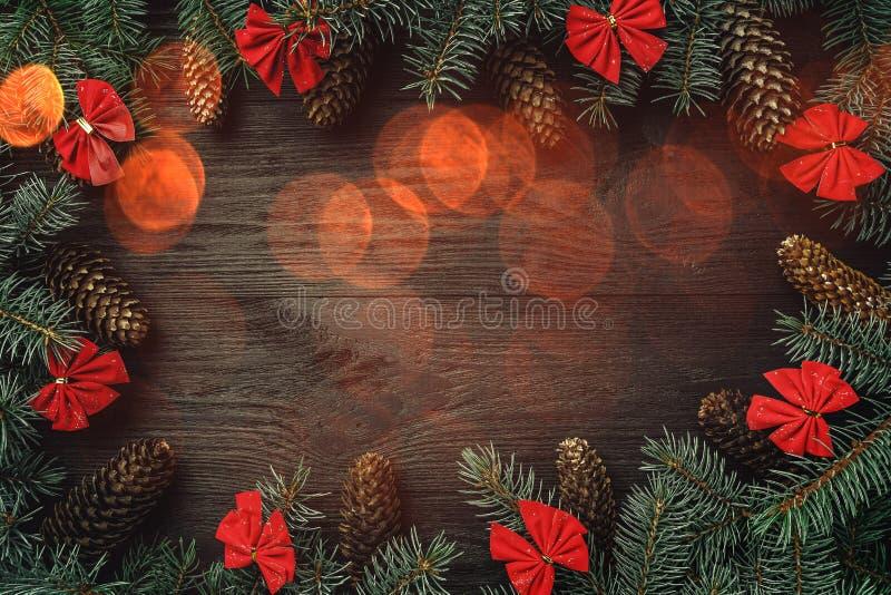 Ευχετήρια κάρτα Χριστουγέννων με την επίδραση λαμπών φωτός Ο υπόλοιπος κόσμος του έλατου διακλαδίζεται με τους κώνους και τα κόκκ στοκ εικόνες