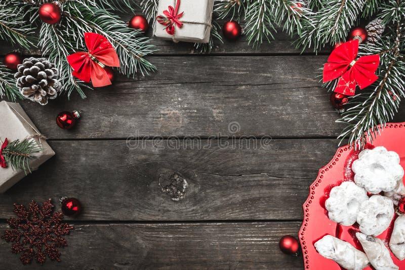 Ευχετήρια κάρτα Χριστουγέννων στο ξύλινο υπόβαθρο, τους κλάδους έλατου, τους κώνους, το διάστημα μηνυμάτων, τα παιχνίδια, τα γλυκ στοκ φωτογραφία με δικαίωμα ελεύθερης χρήσης
