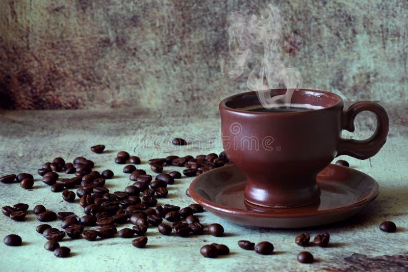 Ευώδης καυτός καφές σε ένα όμορφο φλυτζάνι αργίλου μεταξύ των διεσπαρμένων φασολιών καφέ στοκ εικόνα