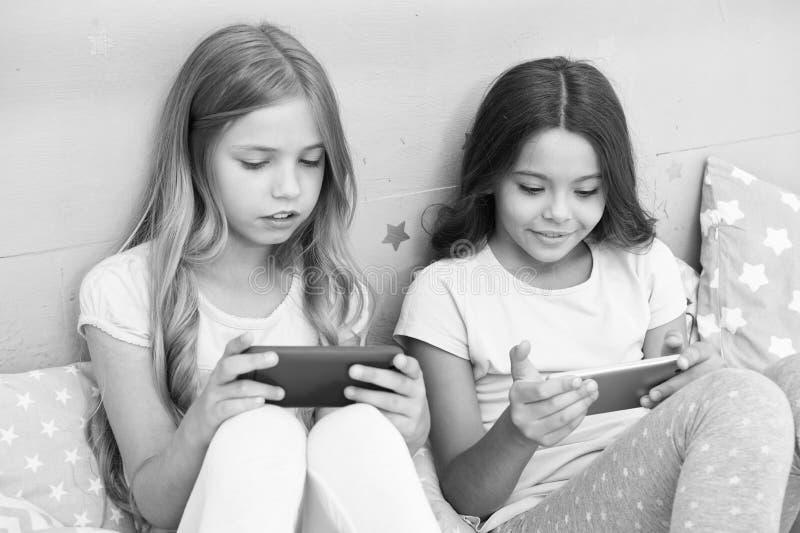 Εφαρμογή για τη διασκέδαση παιδιών Σερφ Διαδικτύου και γονικός συμβουλευτικός απουσίας Πρόσβαση Διαδικτύου Smartphone Οι αδελφές  στοκ εικόνες