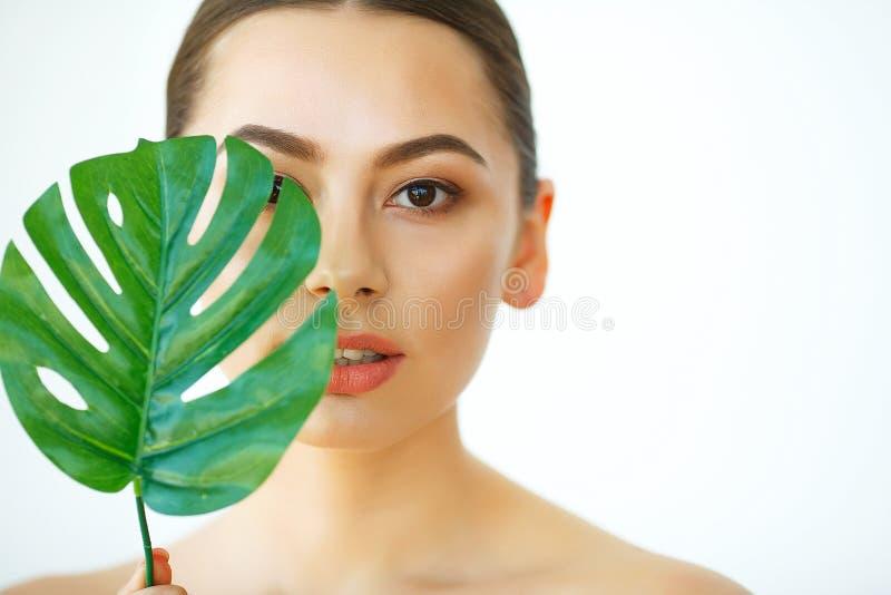 'Εφαρμογή' του διαφανούς βερνικιού δερμάτων προσοχής Πράσινο φύλλο που σκιάζει ένα δεύτερο του όμορφου προσώπου γυναικών Να είστε στοκ εικόνα με δικαίωμα ελεύθερης χρήσης