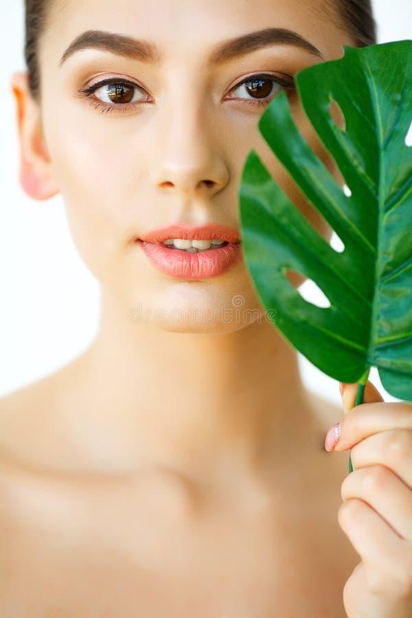 'Εφαρμογή' του διαφανούς βερνικιού δερμάτων προσοχής Όμορφο κορίτσι με τα πράσινα φύλλα επεξεργασία σαπουνιών πετρελαίου σύνθεσης στοκ εικόνες