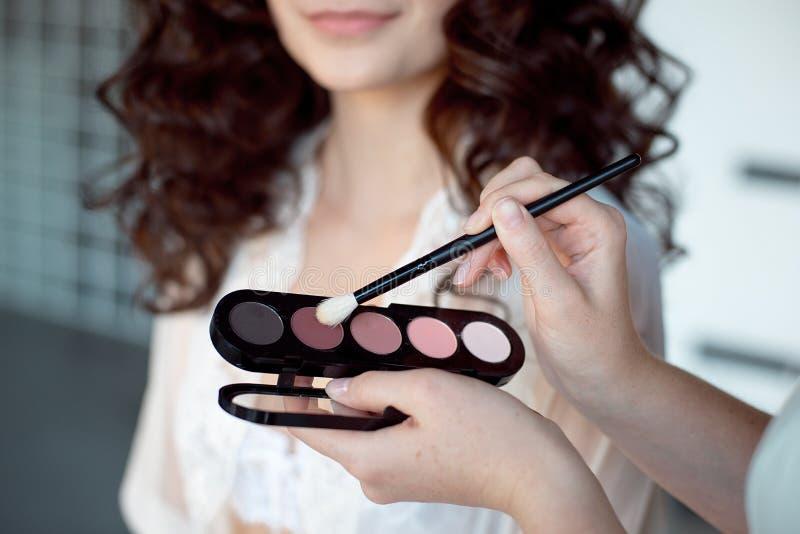 εφαρμόζει τη σκιά ματιών καλλιτεχνών makeup Τέλειο ομαλό δέρμα να ισχύσει makeup Εφαρμογή των σκιών στα πρότυπα μάτια ` s στοκ φωτογραφία με δικαίωμα ελεύθερης χρήσης