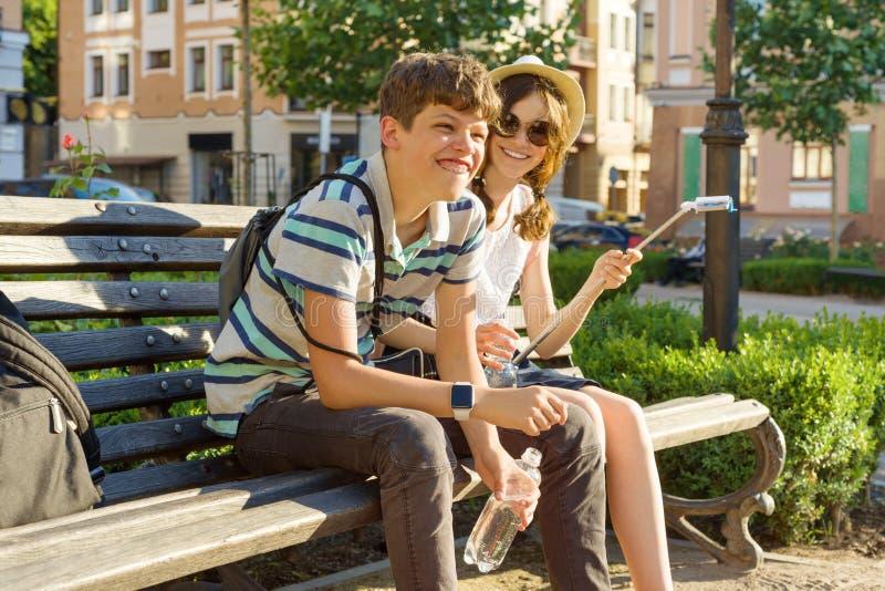 Εφηβική συνεδρίαση κοριτσιών και αγοριών φίλων στον πάγκο στην πόλη, χαμόγελο, ομιλία, που κοιτάζει στο τηλέφωνο Φιλία και έννοια στοκ εικόνα