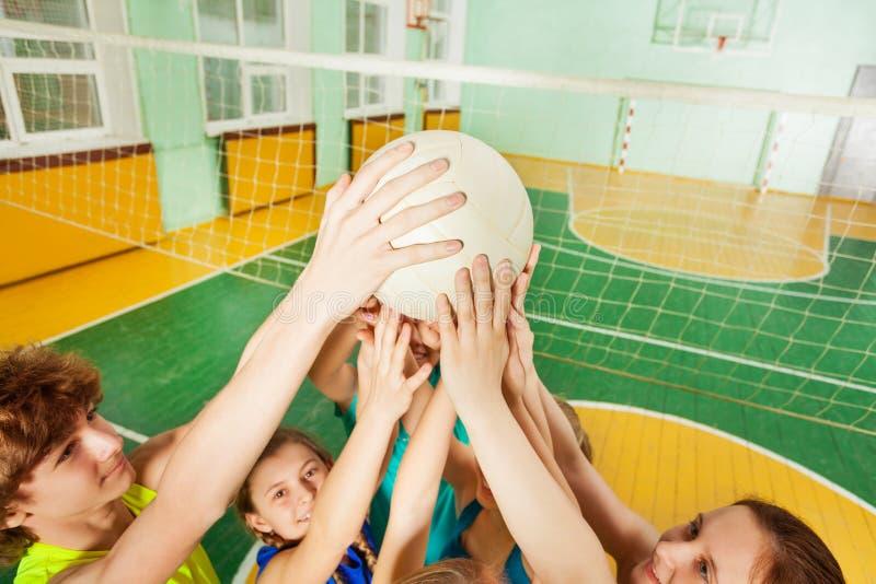 Εφηβικοί παίκτες ομάδων πετοσφαίρισης που εξυπηρετούν μια σφαίρα στοκ εικόνες