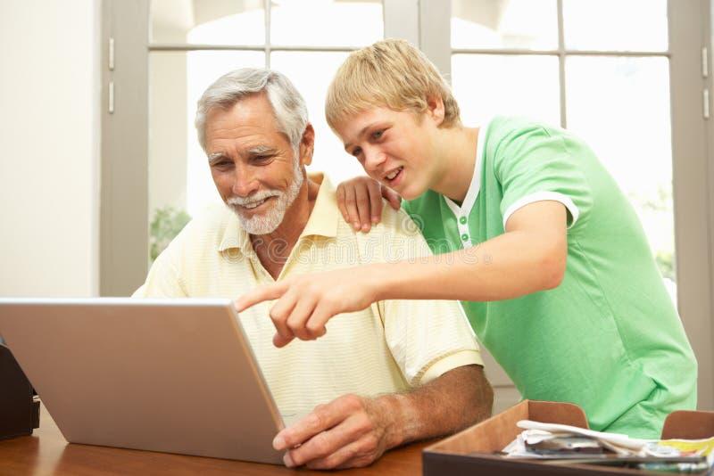 Εφηβικός εγγονός που βοηθά τον παππού για να χρησιμοποιήσει το lap-top στοκ εικόνες με δικαίωμα ελεύθερης χρήσης