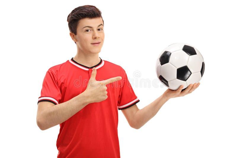 Εφηβικός ποδοσφαιριστής που κρατά ένα ποδόσφαιρο και μια υπόδειξη στοκ φωτογραφία