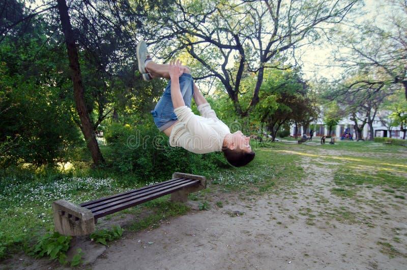 Εφηβικό αγόρι ικανότητας parkour που κάνει το salto προς τα πίσω από τον πάγκο στοκ εικόνα