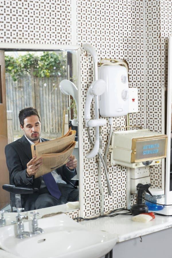 Εφημερίδα ανάγνωσης επιχειρηματιών στο κομμωτήριο στοκ φωτογραφία με δικαίωμα ελεύθερης χρήσης
