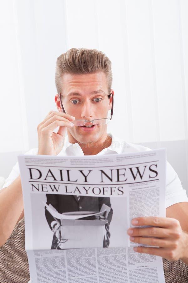 Εφημερίδα ανάγνωσης με τις νέες προσωρινές απολύσεις τίτλων στοκ φωτογραφία