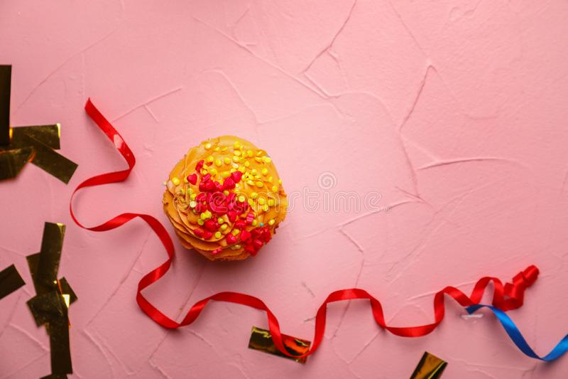 Εύγευστα γενέθλια cupcake με serpentine και το κομφετί στο υπόβαθρο χρώματος στοκ εικόνες