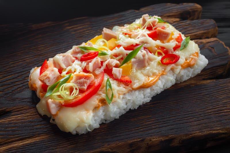 εύγευστα ιαπωνικά τρόφιμα Κομμάτι της πίτσας ρυζιού με εξυπηρετούμενο το μπέϊκον ο στοκ φωτογραφίες