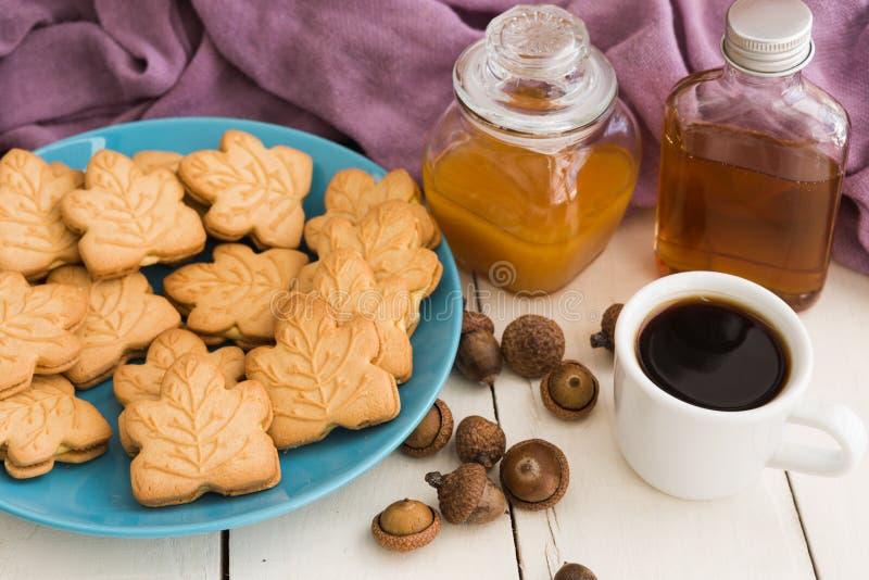Εύγευστα καναδικά μπισκότα κρέμας σφενδάμνου στο μπλε πιάτο με το μέλι, στοκ εικόνες