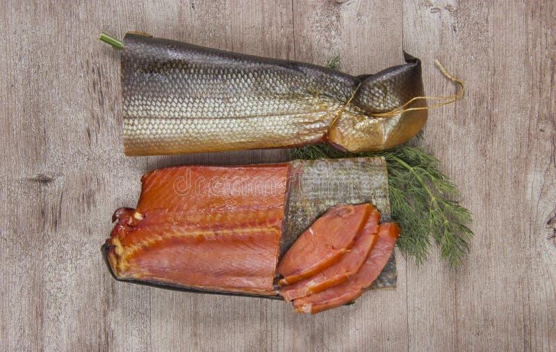 Εύγευστα καπνισμένα ψάρια στο ξύλινο υπόβαθρο στοκ φωτογραφία