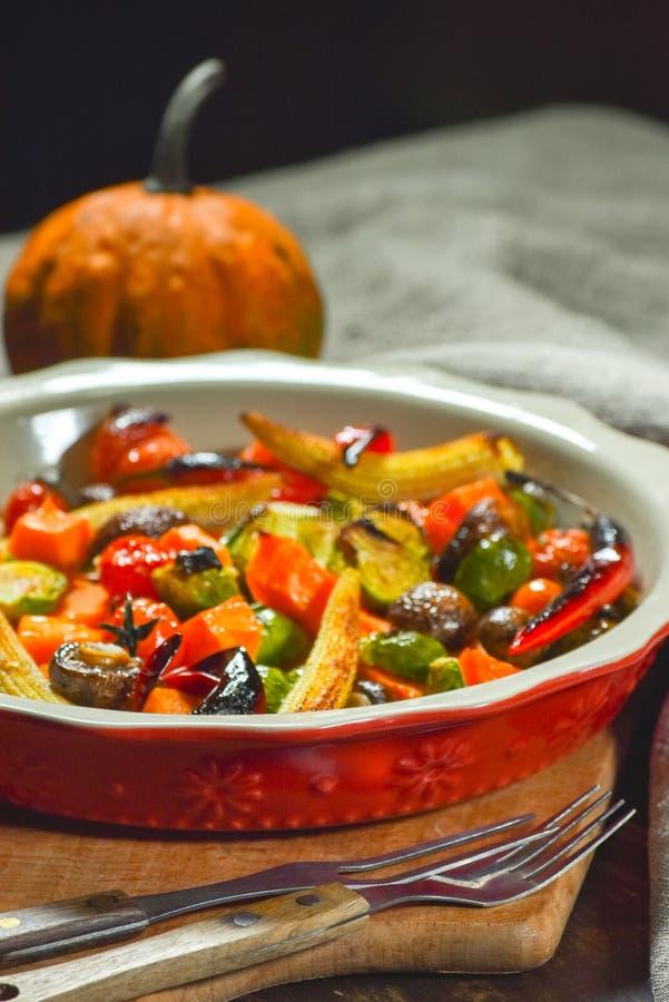 Εύγευστα λαχανικά που ψήνονται στο φούρνο σε ένα κεραμικό πιάτο σε έναν ξύλινο πίνακα Συσκευές, ύφασμα και εξαρτήματα στοκ εικόνες