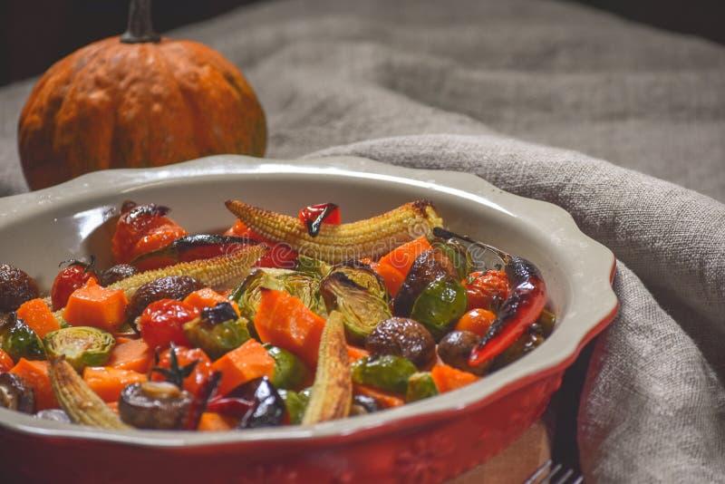 Εύγευστα λαχανικά που ψήνονται στο φούρνο σε ένα κεραμικό πιάτο σε έναν ξύλινο πίνακα Συσκευές, ύφασμα και εξαρτήματα στοκ εικόνα με δικαίωμα ελεύθερης χρήσης