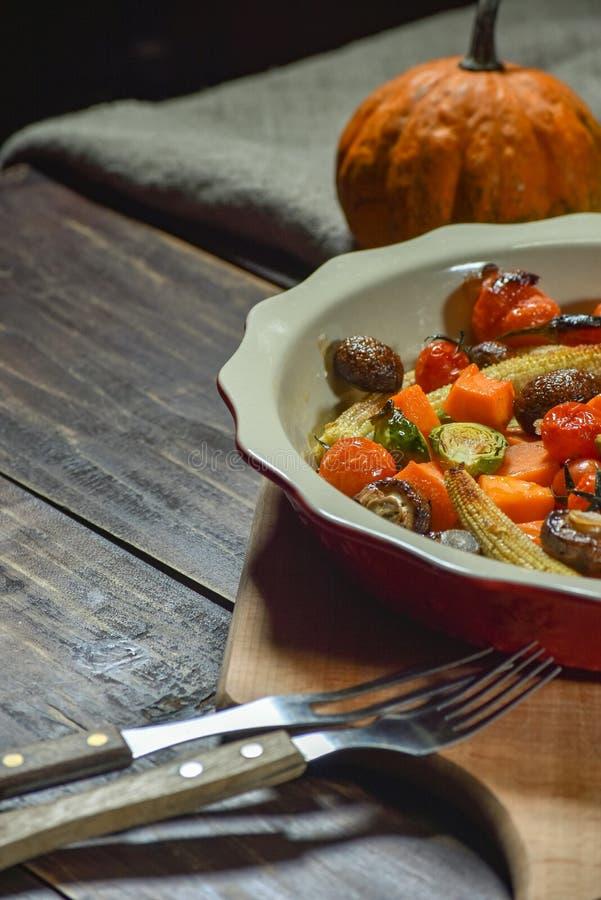 Εύγευστα λαχανικά που ψήνονται στο φούρνο σε ένα κεραμικό πιάτο σε έναν ξύλινο πίνακα Συσκευές, ύφασμα και εξαρτήματα διάστημα αν στοκ φωτογραφία με δικαίωμα ελεύθερης χρήσης