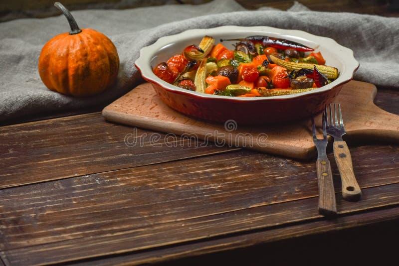 Εύγευστα λαχανικά που ψήνονται στο φούρνο σε ένα κεραμικό πιάτο σε έναν ξύλινο πίνακα Συσκευές, ύφασμα και εξαρτήματα διάστημα αν στοκ εικόνα με δικαίωμα ελεύθερης χρήσης