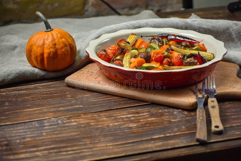 Εύγευστα λαχανικά που ψήνονται στο φούρνο σε ένα κεραμικό πιάτο σε έναν ξύλινο πίνακα Συσκευές, ύφασμα και εξαρτήματα διάστημα αν στοκ εικόνες με δικαίωμα ελεύθερης χρήσης