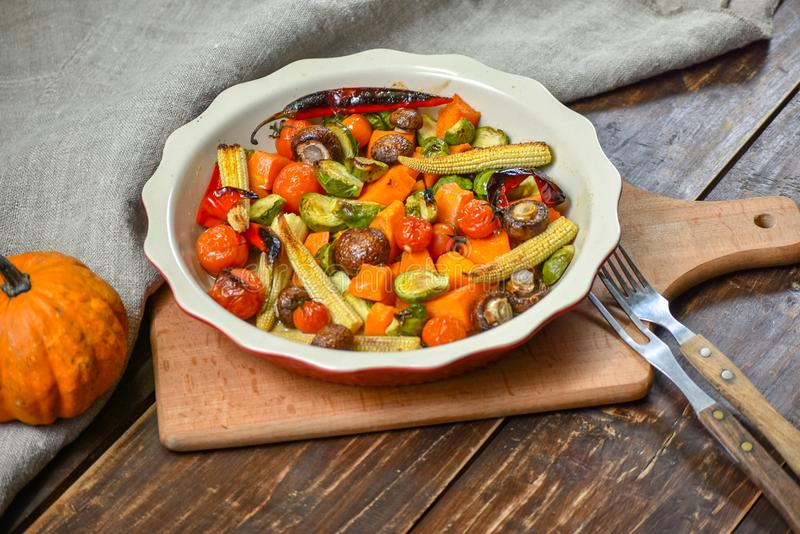 Εύγευστα λαχανικά που ψήνονται στο φούρνο σε ένα κεραμικό πιάτο σε έναν ξύλινο πίνακα Συσκευές, ύφασμα και εξαρτήματα διάστημα αν στοκ φωτογραφία