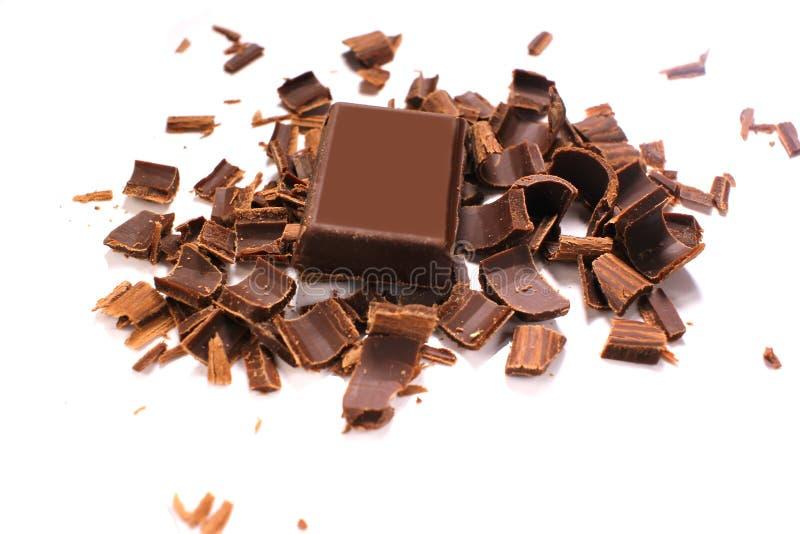 Εύγευστα μαύρα ξέσματα και κομμάτια σοκολάτας στο άσπρο υπόβαθρο, τοπ άποψη στοκ φωτογραφίες