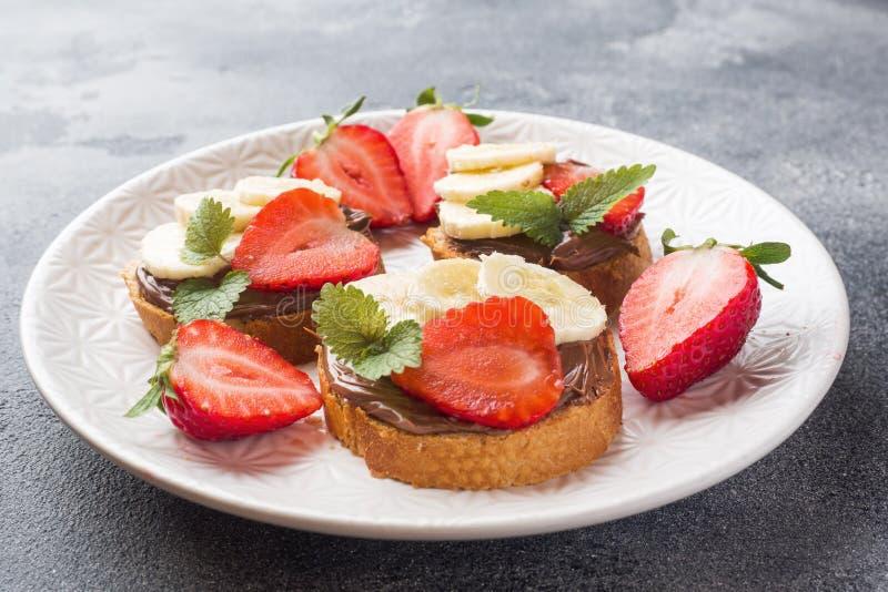Εύγευστα σάντουιτς με nougat, τη φράουλα και την μπανάνα σοκολάτας Έννοια του σκοτεινού συγκεκριμένου υποβάθρου προγευμάτων στοκ εικόνα