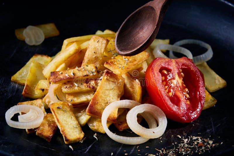 Εύγευστα σπιτικά πικάντικα τηγανητά με το κρεμμύδι και την ψημένη στη σχάρα ντομάτα πέρα από το σκοτεινό υπόβαθρο, εκλεκτική εστί στοκ φωτογραφία με δικαίωμα ελεύθερης χρήσης
