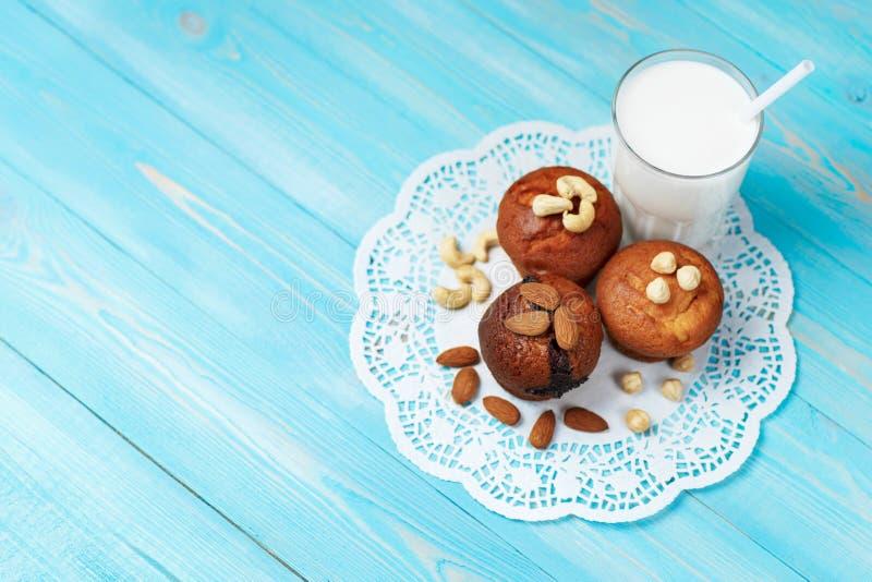 Εύγευστα σπιτικά muffins σοκολάτας και ποτήρι του γάλακτος με τα ανάμεικτα καρύδια στοκ εικόνα με δικαίωμα ελεύθερης χρήσης