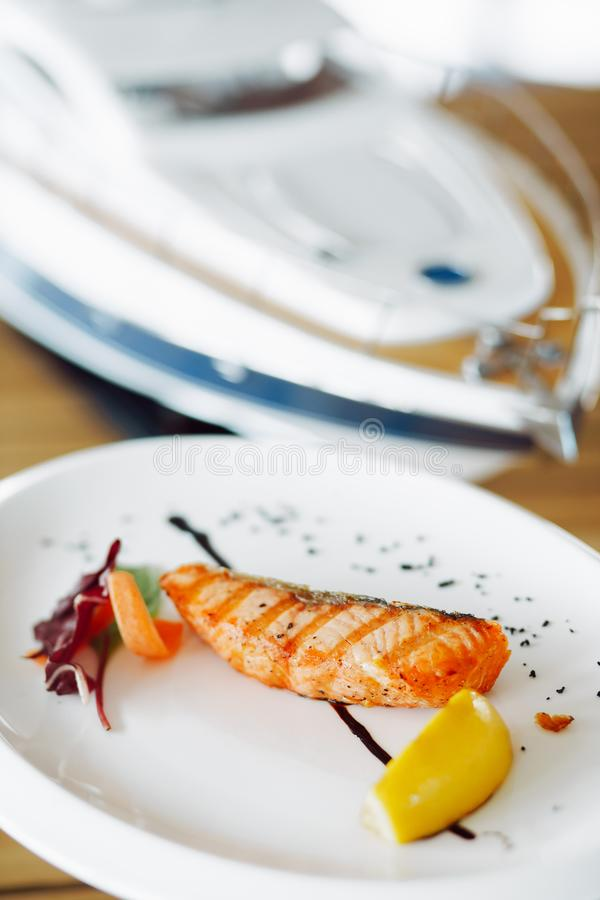 Εύγευστα ψημένα στη σχάρα κόκκινα ψάρια σε ένα άσπρο πιάτο στοκ φωτογραφία με δικαίωμα ελεύθερης χρήσης