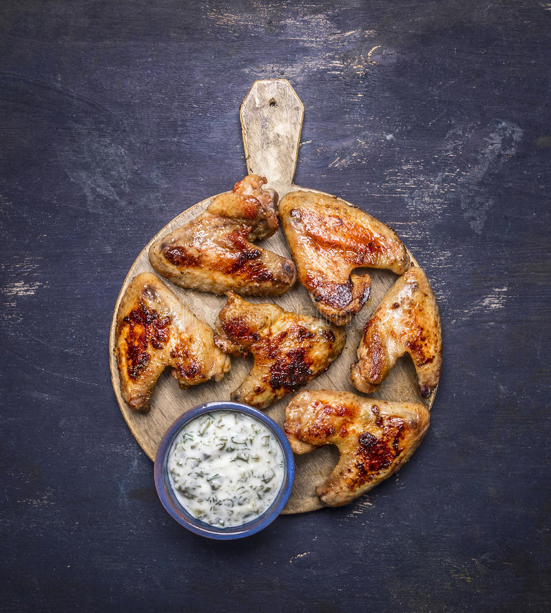 Εύγευστα ψημένα στη σχάρα φτερά κοτόπουλου με τη σάλτσα σκόρδου σε μια στρογγυλή τέμνουσα τοπ άποψη υποβάθρου πινάκων ξύλινη αγρο στοκ εικόνα