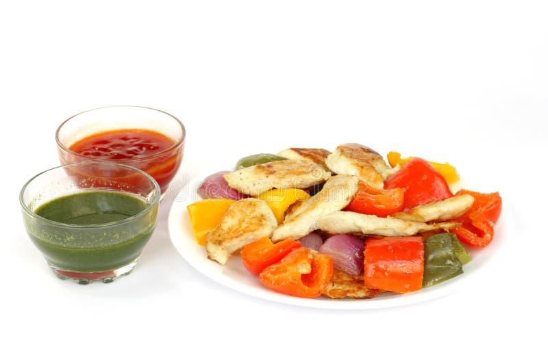 Εύγευστα ψημένα ψάρια, καψικό & κρεμμύδι με την πράσινη & κόκκινη σάλτσα στοκ εικόνες