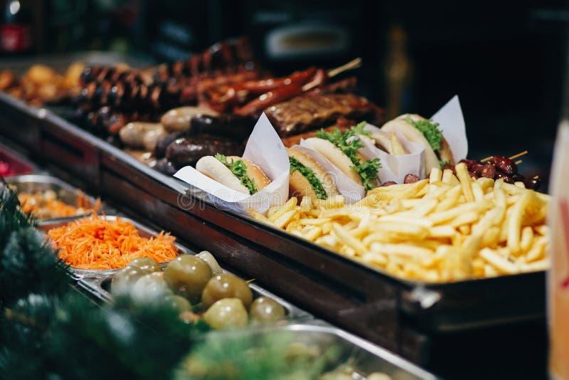 Εύγευστα burgers, τηγανιτές πατάτες και λουκάνικα στην οδό μ διακοπών στοκ εικόνες