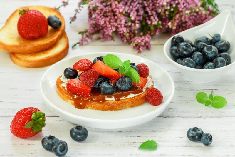 Εύγευστες φρυγανιές σάντουιτς λιχουδιών προγευμάτων με το τυρί κρέμας ή το mascarpone, toffee ίριδων καραμέλας και φρέσκα μούρα στοκ φωτογραφία
