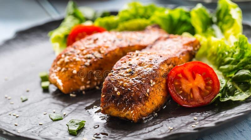 Εύγευστες ψημένες στη σχάρα ψημένες λωρίδες ή μπριζόλες σολομών με τις ντομάτες σουσαμιού και τη σαλάτα μαρουλιού στοκ εικόνες
