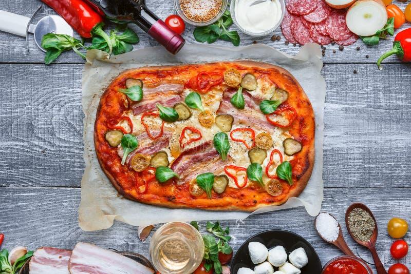 Εύγευστη ιταλική παραδοσιακή πίτσα σε ένα ξύλινο υπόβαθρο με τα συστατικά και ένα μπουκάλι του κόκκινου κρασιού στοκ εικόνα με δικαίωμα ελεύθερης χρήσης