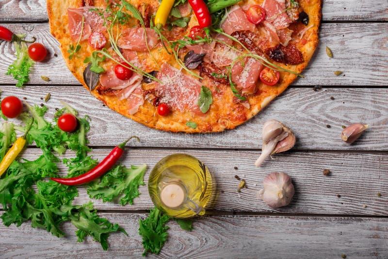 Εύγευστη ιταλική πίτσα σε ένα αγροτικό επιτραπέζιο υπόβαθρο, κινηματογράφηση σε πρώτο πλάνο Ένα δεύτερο της πίτσας κρέατος με τα  στοκ φωτογραφίες με δικαίωμα ελεύθερης χρήσης