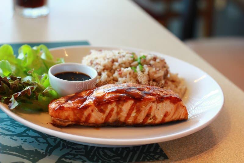 Εύγευστη κόκκινη λωρίδα μπριζόλας σολομών ψαριών σε ένα τηγάνι σχαρών σιδήρου με το ψημένο στη σχάρα πιπέρι κουδουνιών και τις ψη στοκ φωτογραφίες