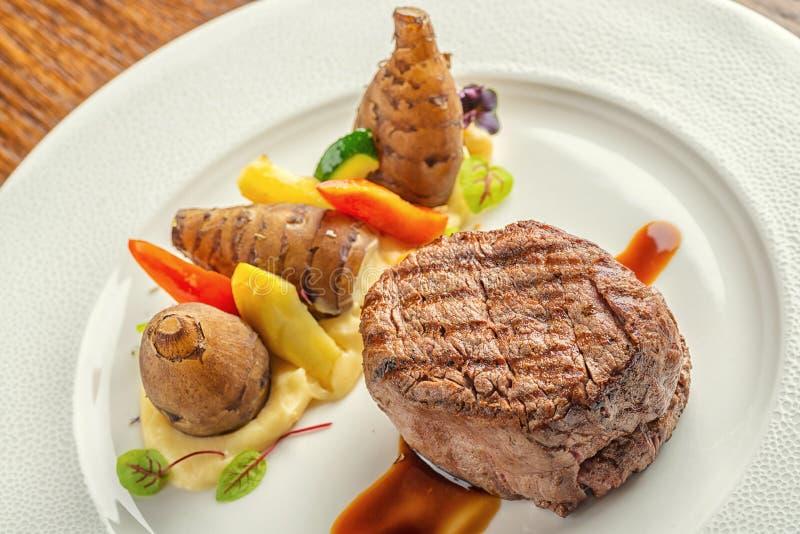 Εύγευστη μπριζόλα βόειου κρέατος με τη σάλτσα και το λαχανικό, που εξυπηρετούνται στο άσπρο πιάτο, τη σύγχρονη γαστρονομία, εστια στοκ εικόνες
