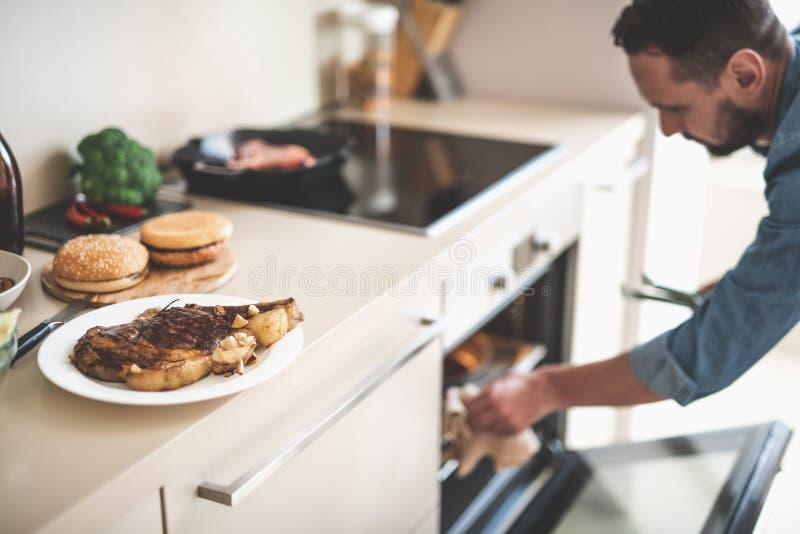 Εύγευστη μπριζόλα βόειου κρέατος στο άσπρο πιάτο και γενειοφόρο άτομο στο θολωμένο υπόβαθρο στοκ εικόνες με δικαίωμα ελεύθερης χρήσης