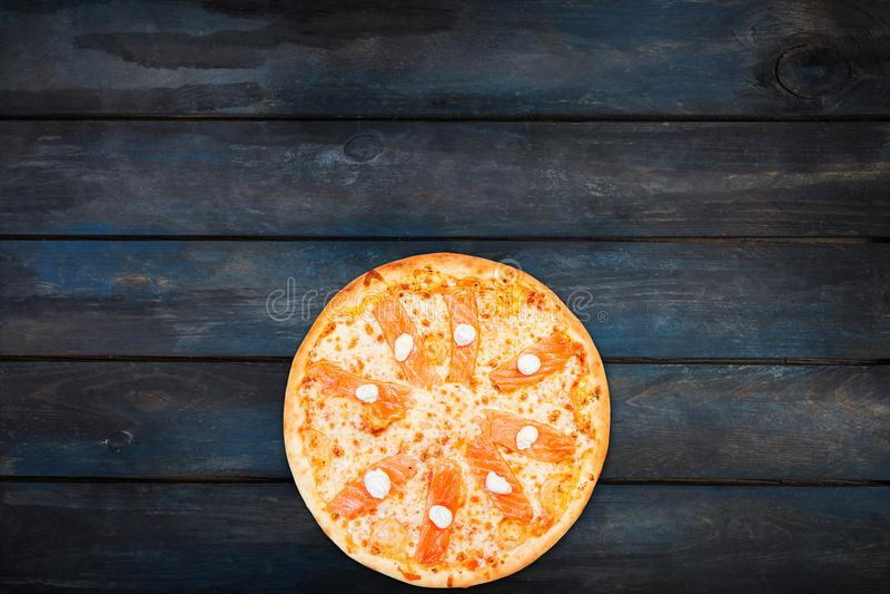 Εύγευστη πίτσα με το σολομό και τυρί της Φιλαδέλφειας σε ένα σκοτεινό ξύλινο υπόβαθρο Τοπ κατώτατος προσανατολισμός άποψης στοκ εικόνες με δικαίωμα ελεύθερης χρήσης