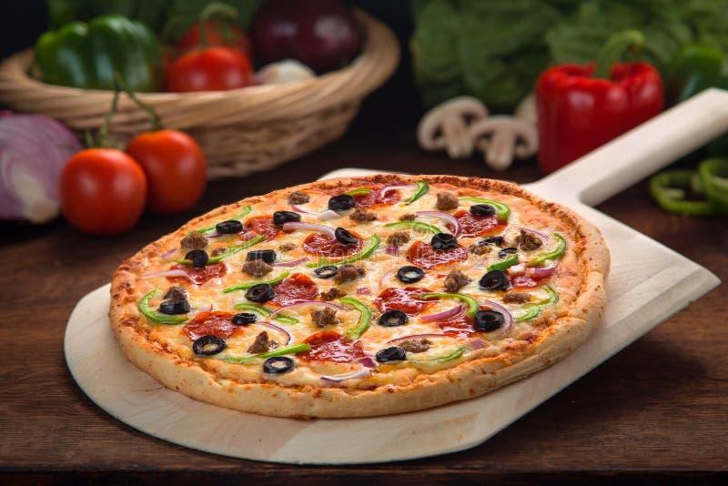 Εύγευστη πλήρης ανώτατη λουξ πίτσα που ψήνεται φρέσκια από το φούρνο δίπλα στα συστατικά στοκ εικόνες