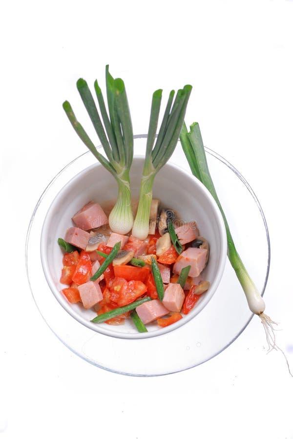 Εύγευστη σαλάτα του ζαμπόν, της ντομάτας, του πιπεριού και του πράσινου κρεμμυδιού σε ένα άσπρο πιάτο o στοκ φωτογραφία με δικαίωμα ελεύθερης χρήσης