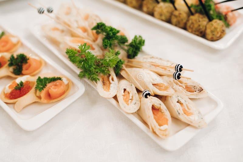 Εύγευστοι ρόλοι και καναπεδάκια ψαριών το κόκκινο χαβιάρι που εξυπηρετείται με στα πιάτα στοκ φωτογραφία με δικαίωμα ελεύθερης χρήσης
