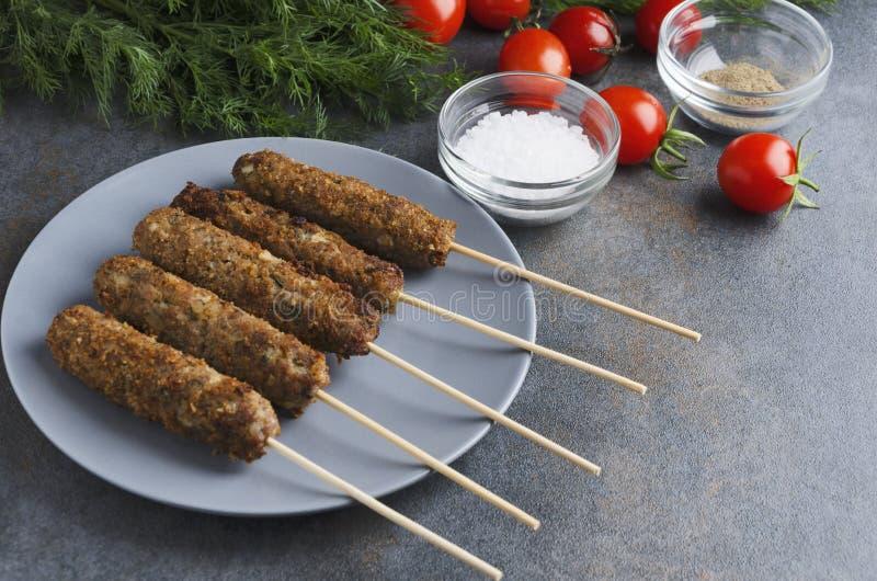 Εύγευστος τύπος kebab με τις ντομάτες, άνηθος, άλας, πιπέρι στον γκρίζο πίνακα στην κουζίνα Φρέσκος που μαγειρεύεται lule kebab στοκ φωτογραφία με δικαίωμα ελεύθερης χρήσης