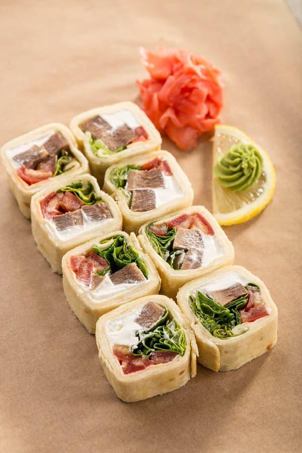 Εύγευστος tortilla ρόλος με το βόειο κρέας, το τυρί και τα λαχανικά με την πιπερόριζα και το wasabi στο υπόβαθρο εγγράφου στοκ εικόνες