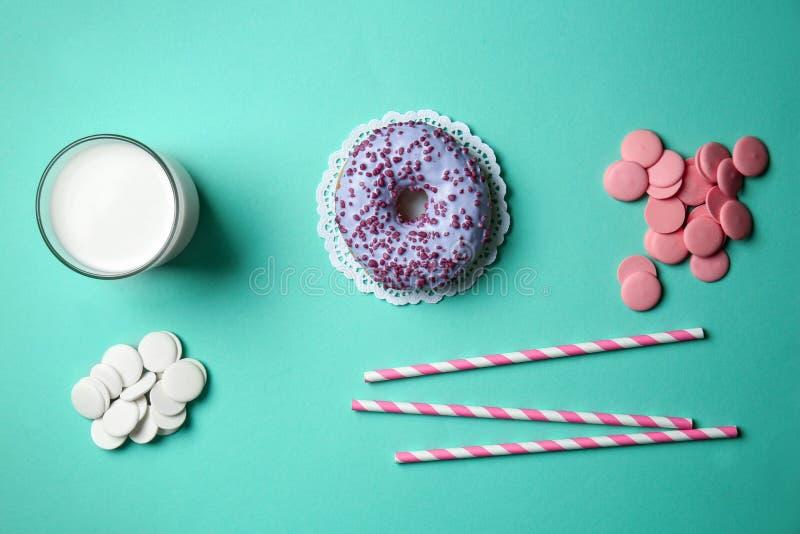 Εύγευστο βερνικωμένο doughnut με τα τσιπ σοκολάτας και το ποτήρι του γάλακτος στο υπόβαθρο χρώματος στοκ εικόνα με δικαίωμα ελεύθερης χρήσης