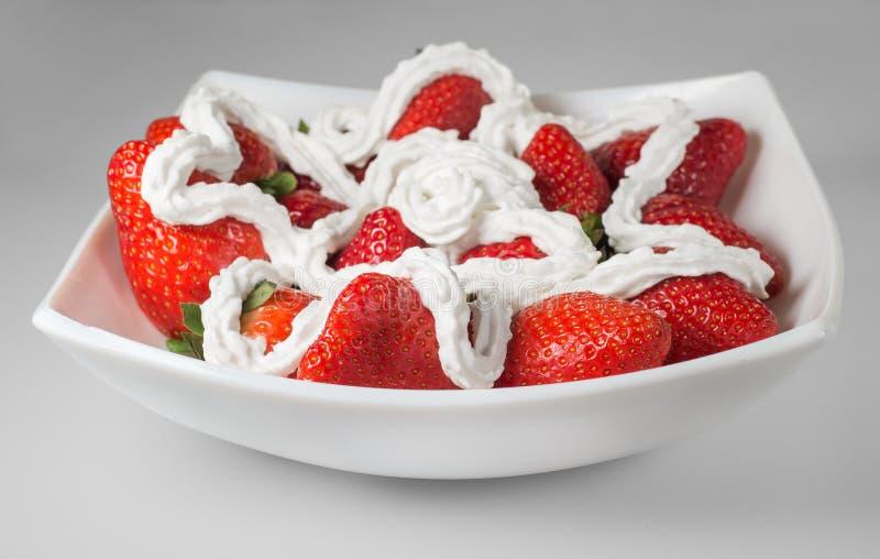 Εύγευστο επιδόρπιο: φράουλες με την κρέμα στο άσπρο πιάτο στοκ εικόνες