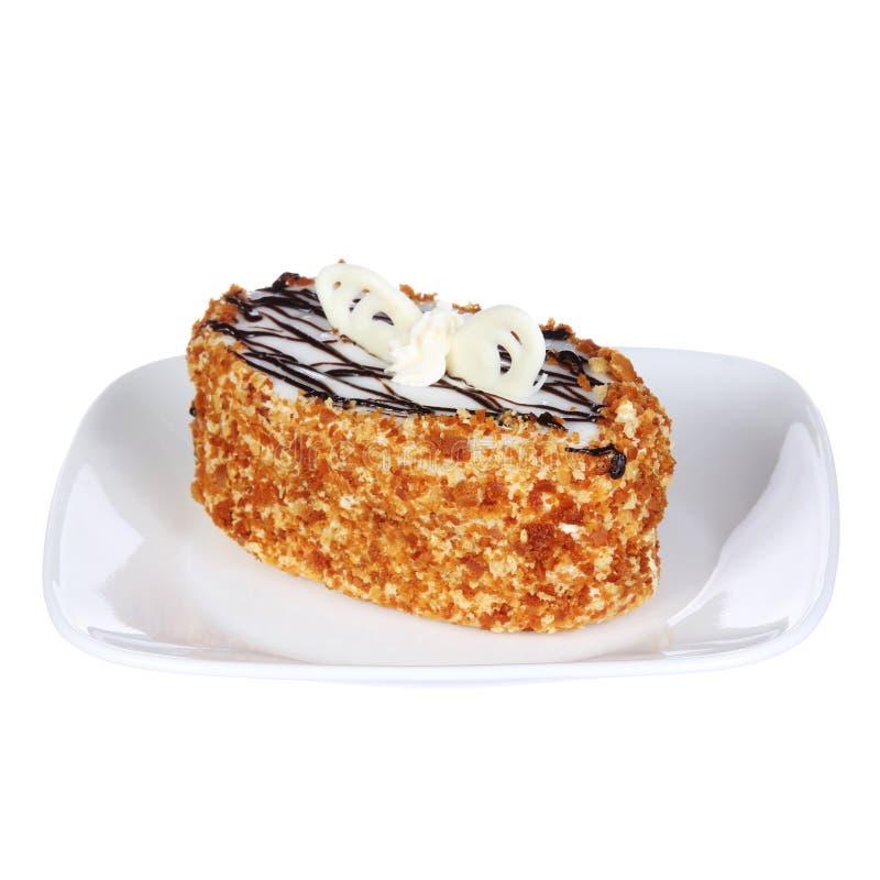Εύγευστο κέικ μελιού με τη σοκολάτα στην κορυφή σε ένα πιάτο, που απομονώνεται στο λευκό στοκ φωτογραφίες
