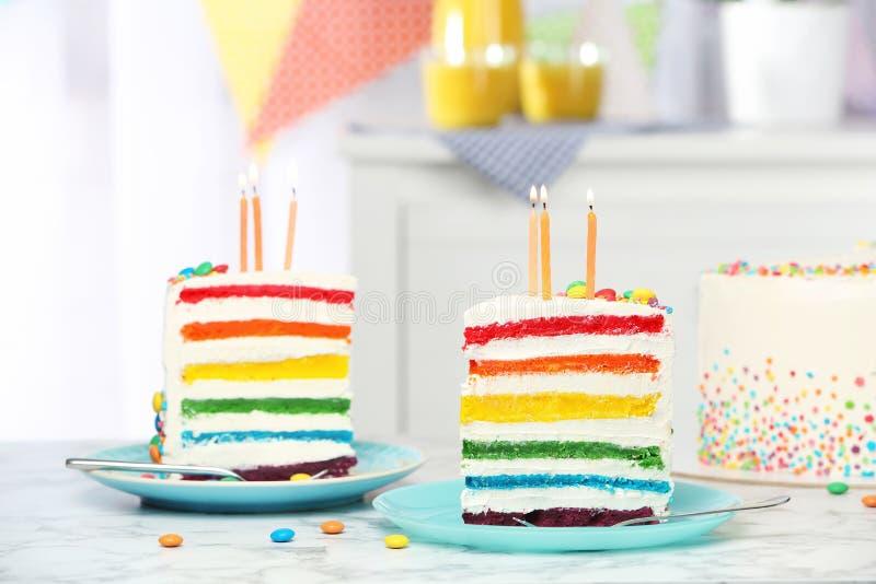Εύγευστο κέικ ουράνιων τόξων με τα κεριά για το κόμμα στοκ φωτογραφία